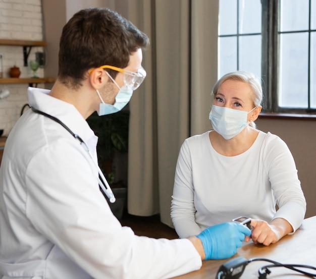 Medico del colpo medio che controlla paziente