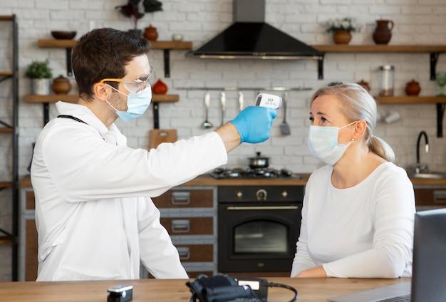 Medico del colpo medio che controlla la temperatura della donna