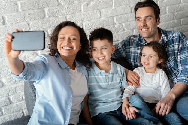 Famiglia del colpo medio che prende i selfie