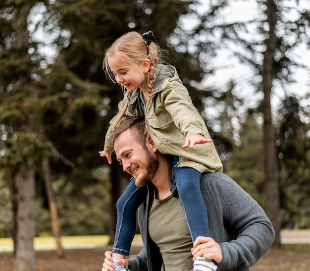 Padre del colpo medio che trasporta la ragazza sulle spalle Foto Premium