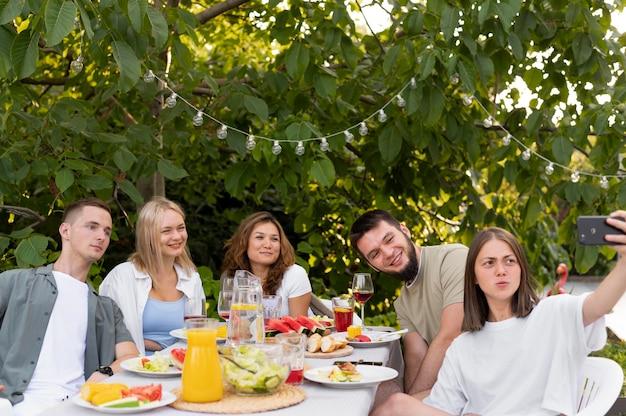 Amici di tiro medio che si fanno selfie con il cibo