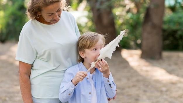 Nipote di tiro medio che mangia zucchero filato