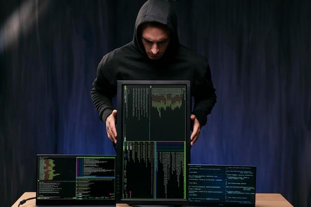 Hacker a tiro medio che tiene monitor
