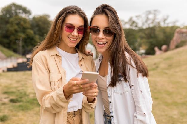 Ragazze felici del colpo medio che esaminano telefono