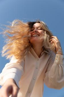 Donna felice del colpo medio alla spiaggia
