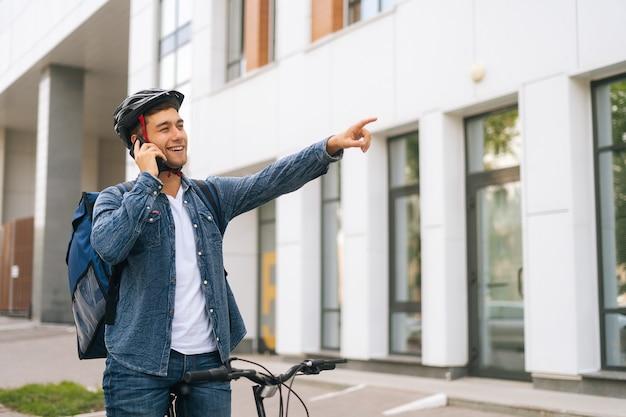 Colpo medio di un bell'uomo di consegna gioioso con zaino termico che parla al telefono cellulare, vede il cliente e segna la posizione alzando la mano. fattorino in casco protettivo utilizzando smartphone all'aperto.