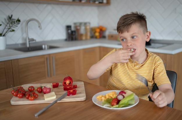 Ragazzo del colpo medio che mangia verdura