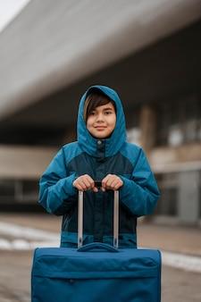 Ragazzo di tiro medio che tiene i bagagli all'aperto