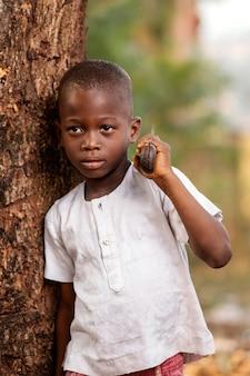 Ragazzo del colpo medio che posa vicino all'albero