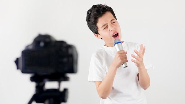Bambino di colpo medio che canta sulla macchina fotografica