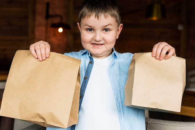 Bambini di tiro medio che tengono i sacchetti di carta