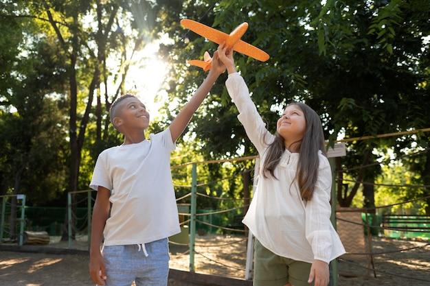 Bambini di tiro medio che giocano con l'aereo
