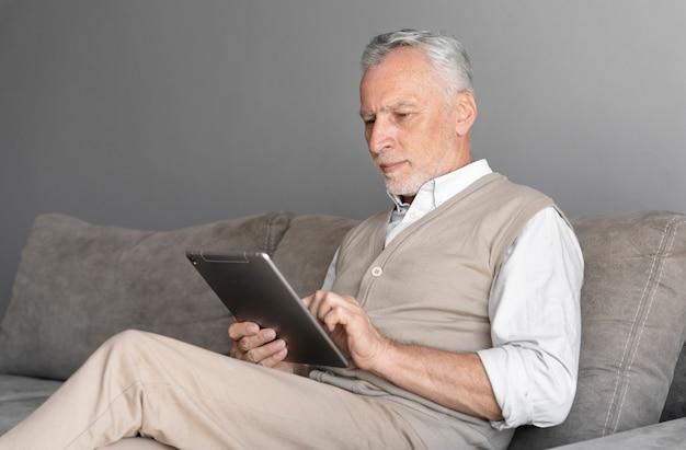 Uomo con colpo medio che tiene tablet