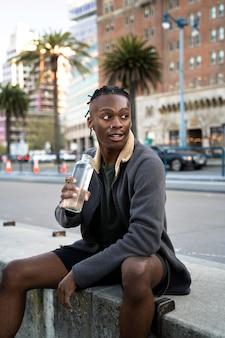 Uomo con colpo medio che tiene in mano una bottiglia d'acqua