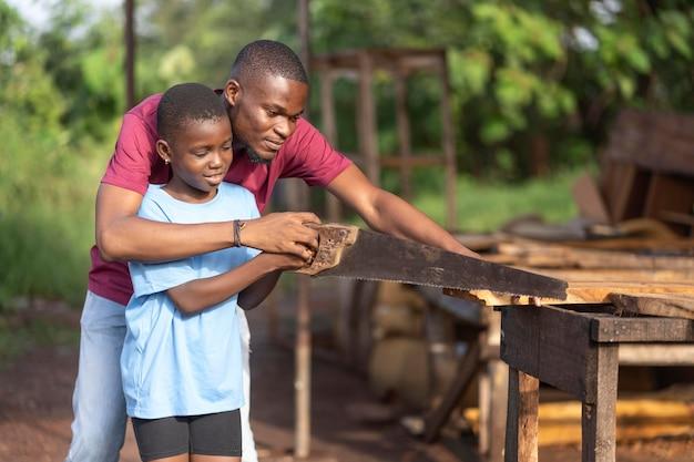 Uomo e bambino a tiro medio con sega a mano