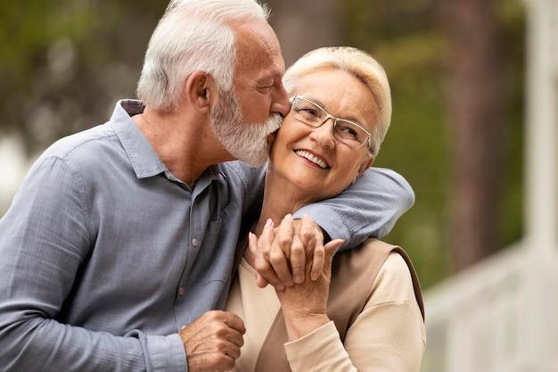 Uomo del colpo medio che bacia la donna sulla guancia