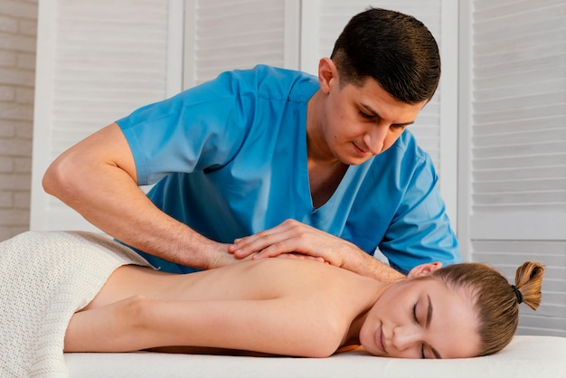 Uomo del colpo medio che massaggia la schiena della donna