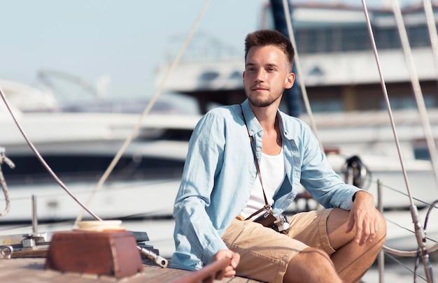 Uomo del colpo medio che posa sulla barca
