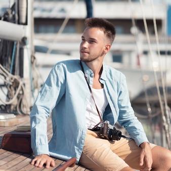 Uomo del colpo medio che si siede sulla barca
