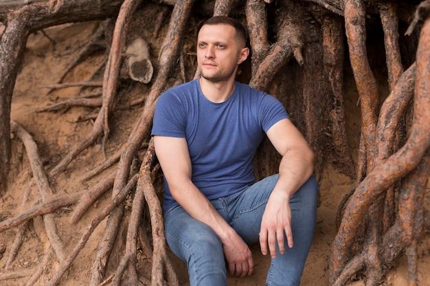 Uomo del colpo medio seduto vicino alle radici degli alberi