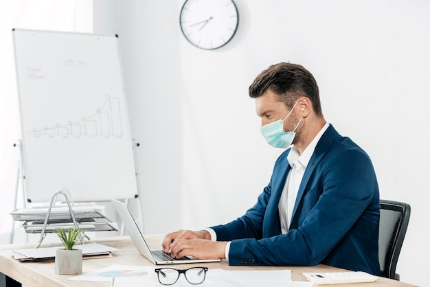 Uomo del colpo medio che digita sul computer portatile
