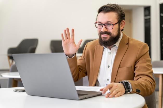 Uomo del colpo medio che fluttua al computer portatile