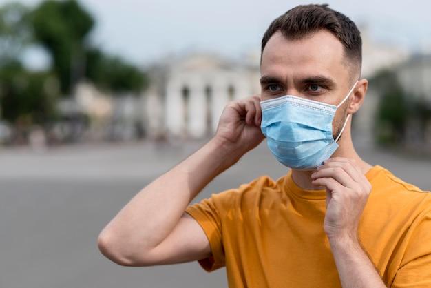 Uomo di tiro medio che indossa maschera medica