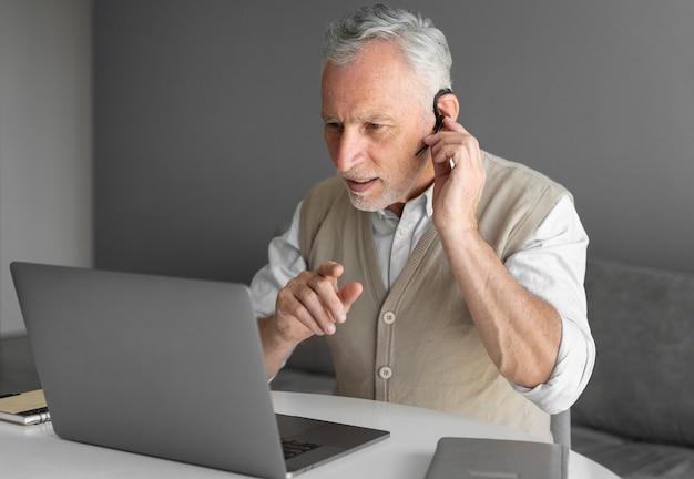 Uomo di tiro medio con laptop e auricolare