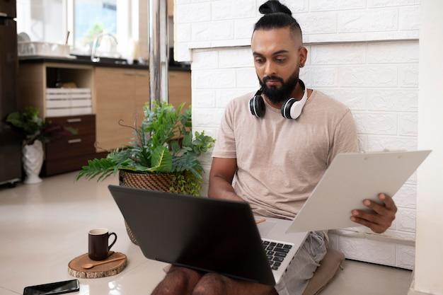 Uomo del colpo medio che lavora con il computer portatile