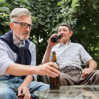 Uomini di tiro medio che bevono birra
