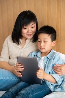 Colpo medio madre e figlio con tablet
