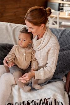 Madre a tiro medio che tiene in braccio il bambino sul divano