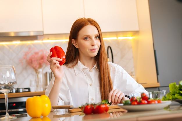 Ritratto a colpo medio di una giovane donna rossa attraente che tiene in mano peperoni rossi seduti a
