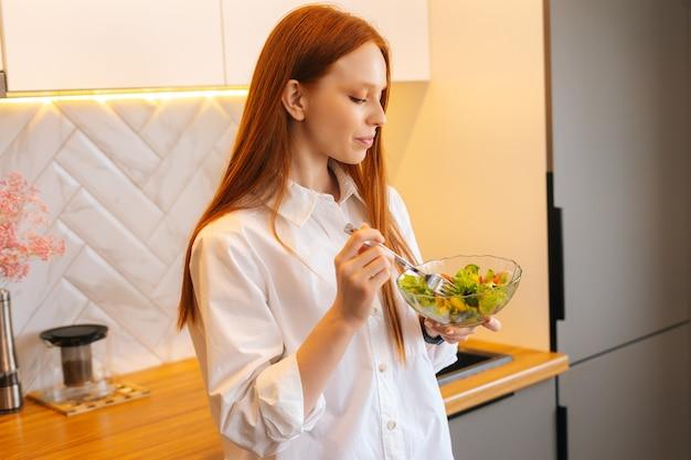 Ritratto a colpo medio di una giovane donna rossa abbastanza attraente che mangia insalata vegetariana fresca godendosi