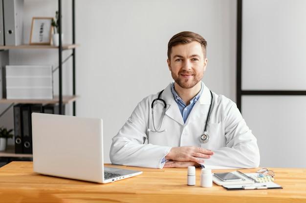 Medico di smiley del colpo medio alla scrivania