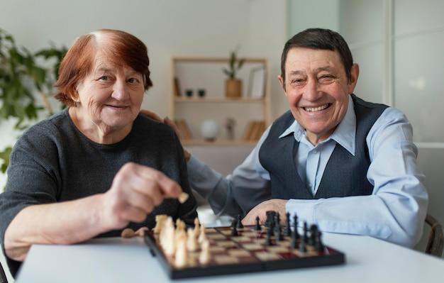Anziani di smiley del colpo medio che giocano a scacchi