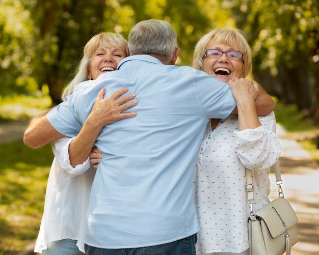 Amici sorridenti a colpo medio che si abbracciano