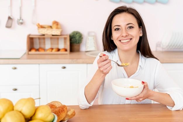 Ragazza di smiley del colpo medio che mangia i cereali