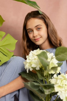 Ragazza di smiley del colpo medio che posa con i fiori