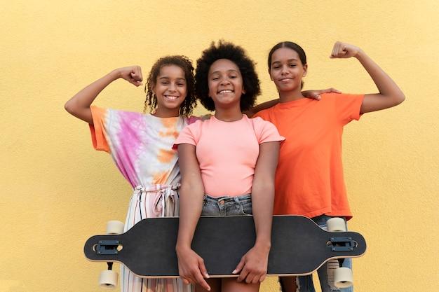 Ragazze smiley a tiro medio con skateboard