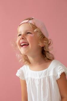 Ragazzo sorridente con colpo medio che indossa un cappello rosa