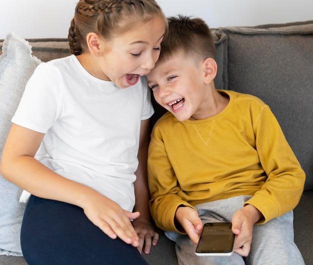 Bambini sorridenti a colpo medio con telefono