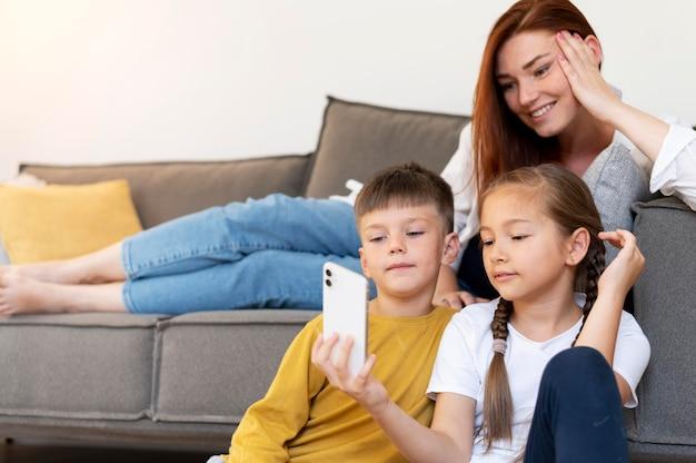 Donna sorridente e bambini di colpo medio che prendono selfie