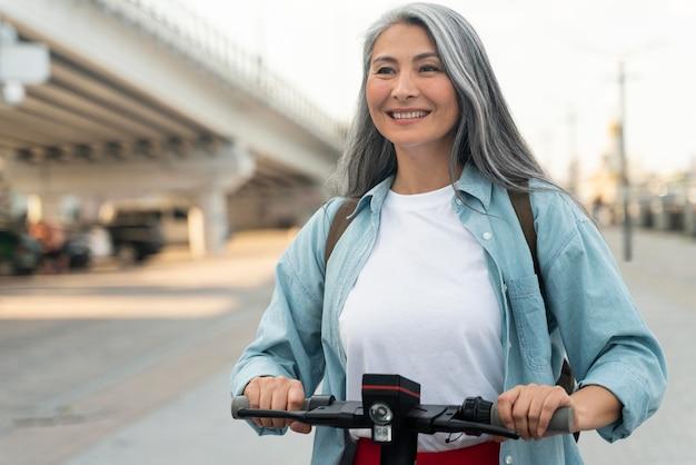 Donna sorridente di colpo medio su scooter
