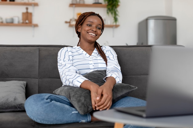 Donna sorridente di colpo medio che si siede sul divano