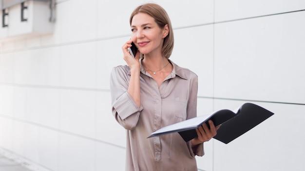Donna di smiley del colpo medio che parla sul telefono