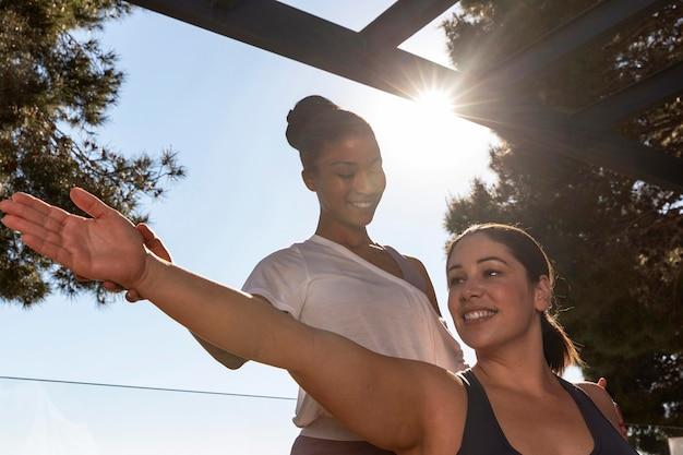 Donne di smiley colpo medio che fanno yoga