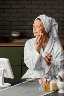 Donna del colpo medio che applica crema per il viso