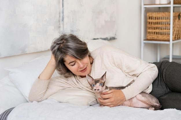 Colpo medio donna e gatto a letto