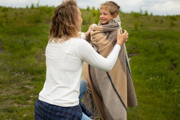Colpo medio donna che copre bambino